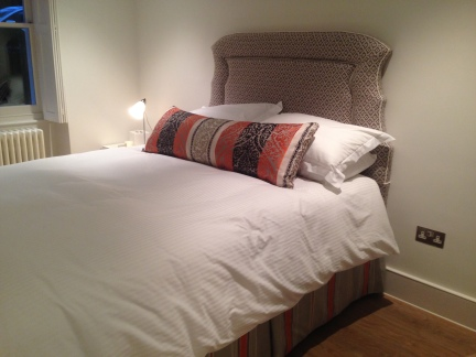 modern style headboard with oversized scatter and striped valance